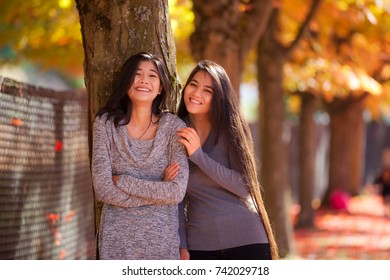 Two biracial teen girls or young women standing next to maple tree with colorful autumn leaves