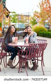 Two biracial teen girls or young women sitting together drinking boba tea at cafe, pointing and looking over at side
