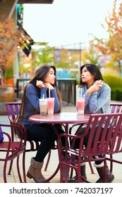 Two biracial teen girls or young women sitting together drinking boba tea at cafe, talking