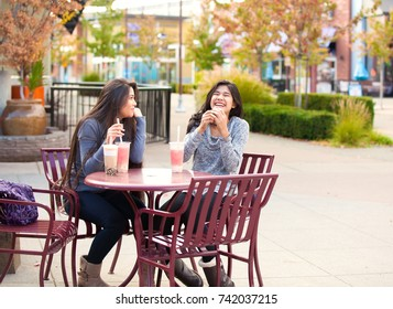 Two biracial teen girls or young women sitting together drinking boba tea at cafe, laughing and smiling