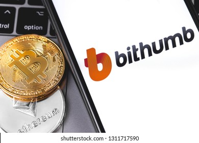 Two bitcoins, Bithumb logo of crypto-exchange on the screen smartphone. Bithumb is popular largest cryptocurrency exchange on the market. Moscow, Russia - February 13, 2019