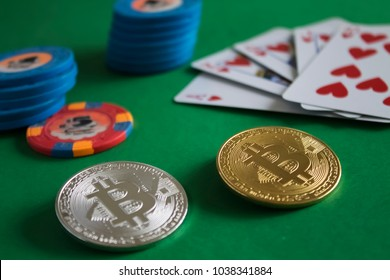 Two bitcoins laying down on green poker table and bunch of chips with cards in the background|gold|silver|blue|flush