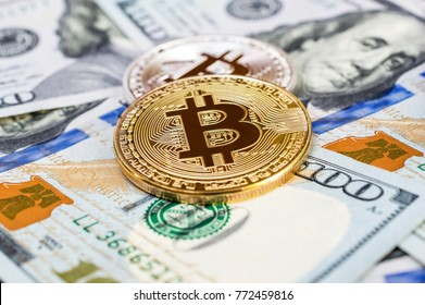 Two bitcoins on dollars background. Business concept.