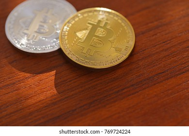 Two Bitcoins on a wooden surface.