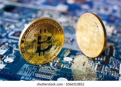Two bitcoins standing on the electronic motherboard of a laptop