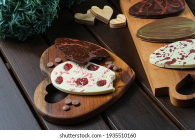 Two bitten 2D Easter eggs (ovos de Páscoa) on a heart-shaped plate. Next to chocolate callets, other 2D eggs and small wooden hearts.
