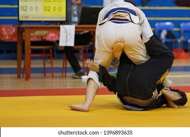Two BJJ brazilian jiujitsu fighters at the tournament fighting jiu jitsu single X guard