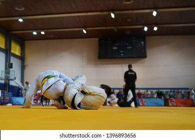 Two BJJ brazilian jiujitsu fighters at the tournament fighting jiu jitsu leg lock attack