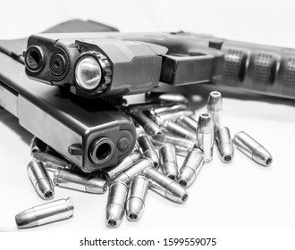 Two black 9mm pistols stacked together on top of 9mm hollow point bullets on a white background shot in black and white