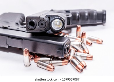 Two black 9mm pistols stacked together on top of 9mm hollow point bullets on a white background