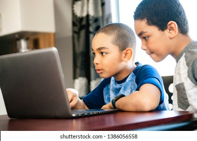 two Black boy sitting playing on a laptop computer at home
