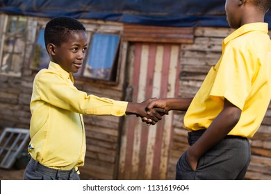 Two black boys shaking hands while looking at each other.