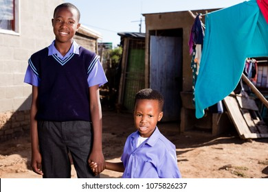 Two black brothers in a township holding hands with a happy expression.