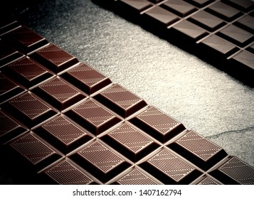 Two black chocolate bars on black slate plate, top view