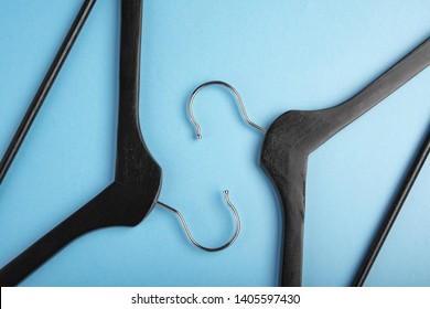 Two black coat hangers facing each other. Design concept. Flat lay. Copy space for text.