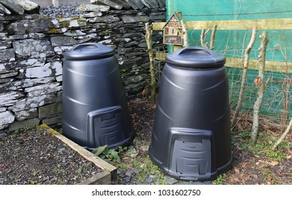 Two black compost bins in a winter vegetable garden in Wales.