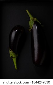 Two Black eggplants on black background