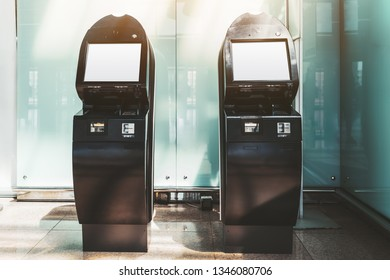 Two black electronic check-in counters in the departure area of the airport terminal or railway station depot with empty white screen mockups; templates of blank LCD screens of self-service terminals