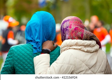 Two black female refugees in the Netherlands seen from the back. Both women wear a colorful scarf.