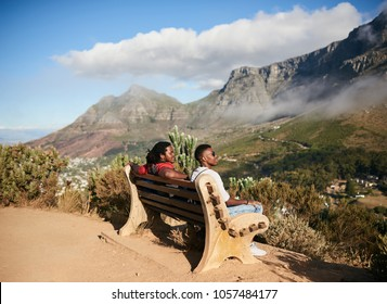 Two black guys sitting together on a public bench next to a hiking trail with an epic view of the mountainous terrain and mystical clouds on a warm summers day in bright sunlight.