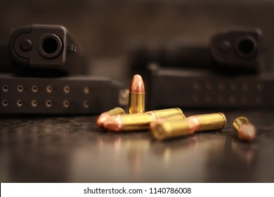 Two black handguns resting on their magazines with 9mm bullets in front.