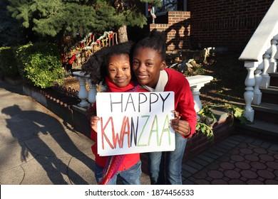 Two black kids holding Happy Kwanzaa outside urban home