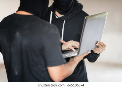 Two black masked hackers are using laptop in them hand. They are trying to  hack data. Selective focus at far hacker' hand.