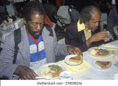 Two black men eating Christmas dinner at homeless shelter, Los Angeles, California