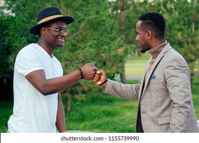 two black men in stylish suits meeting in a summer park. African-Americans friends hispanic businessman embrace hug greeting each other teamwork outdoors. successful deal concept