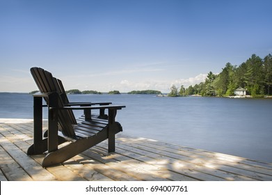 Two black Muskoka chairs sitting on a wood dock facing a lake. Across the calm water is a white cottage nestled among green trees. Canada flag is visible
