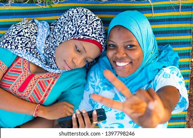 two black muslim girls lying down on a mat one using her phone and the other smiling and looking up
