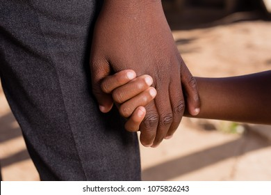 Two black people holding hands.