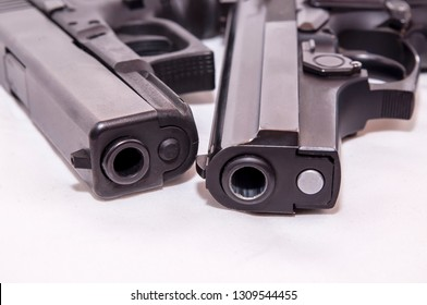 Two black pistols, a 40 caliber and a 9mm laying together on a white background