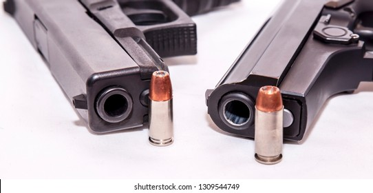 Two black pistols, a 9mm and a 40 caliber each with a bullet to it on front of the muzzle on a white background
