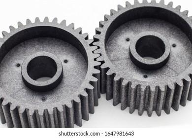 Two black plastic cog gears near