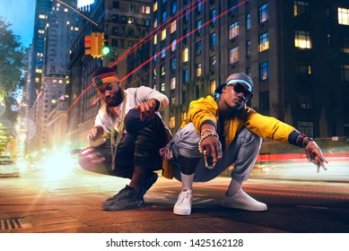 Two black rappers dancing on city street