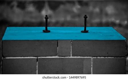 Two black screws on a blue concrete surface