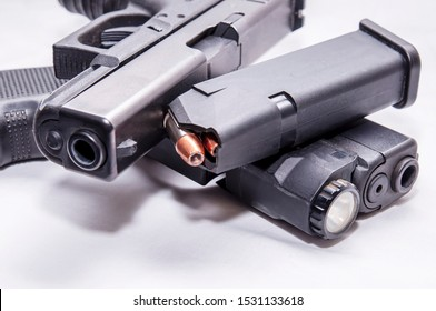 Two black semi automatic 9mm pistols with a loaded pistol magazine along with ammunition on a white background