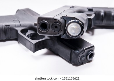 Two black semi automatic 9mm pistols, one with a flashlight attached below the muzzle on a white background