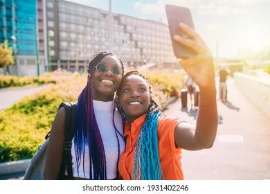 Zwei schwarze Schwestern im Freien, die sich mit Smartphone-Hintergrundbeleuchtung selbst machen, lächeln und mit guten positiven Vibes lachen