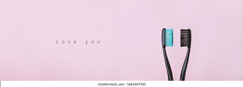 Two black toothbrushes on pink. Relationship between man and woman, Valentines Day and love concept. Banner with copyspace and text. Stock photo.
