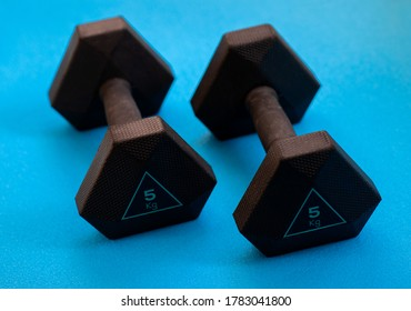 Two black weights 5 kg on the blue background