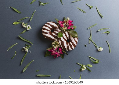 Two black and white chocolate doughnuts decorated with plants and flowers on a black paper background, seen from above