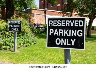 Two black and white  reserved parking only signs located at Warrington Town Hall Bank Park Warrington Cheshire May 2018