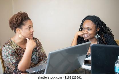 Two black women doing work on laptops
