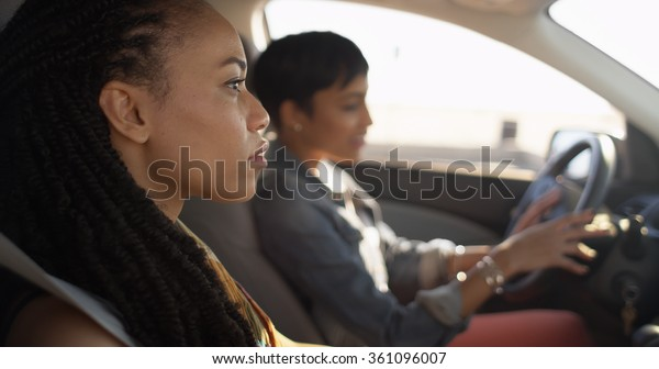 Two black women friends sitting in car talking to each other