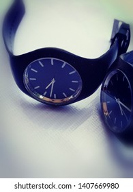 Two black wristwatches, blue dial, time difference