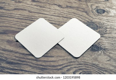 Two blank beer coasters on wooden background. Responsive design mockup.