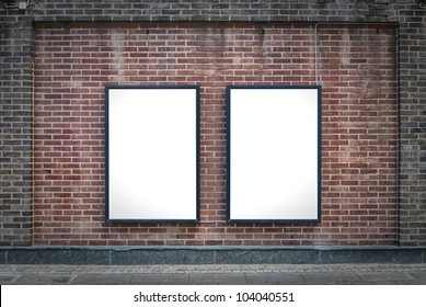 Two blank billboards attached to a buildings exterior brick wall.