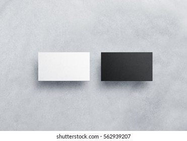 Two blank business card mockups isolated on grey textured background. Black and white namecard design mock up presentation. Empty horizontal visiting paper sheets template with shadows.